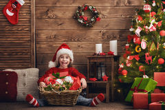 La muchacha está adornando el árbol de navidad Fotos de archivo