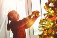 La muchacha está adornando el árbol de navidad Fotografía de archivo