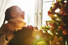 La muchacha está adornando el árbol de navidad Imagen de archivo
