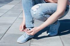 La muchacha está atando cordones en las zapatillas de deporte foto de archivo libre de regalías