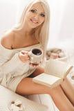 La muchacha está bebiendo el café y está leyendo un libro Imágenes de archivo libres de regalías