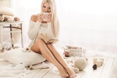 La muchacha está bebiendo el café y está leyendo un libro Fotos de archivo libres de regalías