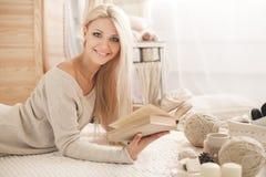 La muchacha está bebiendo el café y está leyendo un libro Fotografía de archivo libre de regalías
