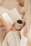 La muchacha está bebiendo el café y está leyendo un libro Imagen de archivo