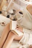 La muchacha está bebiendo el café y está leyendo un libro Foto de archivo