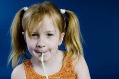 La muchacha está bebiendo la naranja Imágenes de archivo libres de regalías