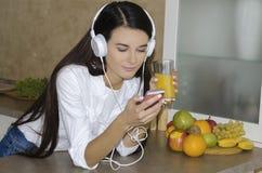 La muchacha está bebiendo un vidrio de zumo de naranja fresco Imagenes de archivo