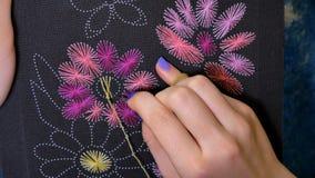 La muchacha está bordando las flores cerca para arriba metrajes