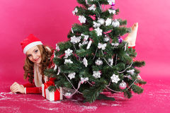 La muchacha está buscando los regalos cerca del árbol de navidad Fotos de archivo libres de regalías