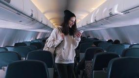 La muchacha está buscando su asiento en el avión almacen de metraje de vídeo