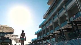 La muchacha está caminando cerca de la piscina del hotel de la playa metrajes