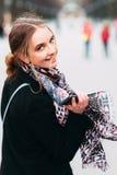La muchacha está caminando con un teléfono móvil Fotografía de archivo libre de regalías