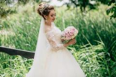La muchacha está caminando en un vestido enorme del cordón en un campo liso con la hierba alta en su día de boda Un manojo hermos fotografía de archivo