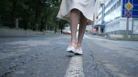La muchacha está caminando a lo largo de las marcas de camino almacen de metraje de vídeo