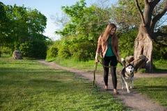 La muchacha está caminando a lo largo del sendero con su perro Foto de archivo