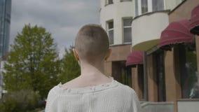 La muchacha está caminando a través de las calles metrajes