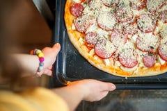 La muchacha está cocinando la pizza imagen de archivo