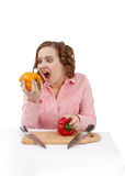 La muchacha está comiendo la pimienta. foto de archivo