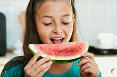 La muchacha está comiendo la sandía Imagen de archivo libre de regalías