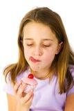 La muchacha está comiendo las tortas de lujo Imagen de archivo libre de regalías
