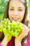 La muchacha está comiendo las uvas Imagenes de archivo