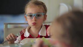 La muchacha está comiendo para la salchicha asada a la parrilla almuerzo con los purés de patata almacen de metraje de vídeo