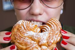 La muchacha está comiendo un anillo de las natillas - un postre ruso tradicional fotos de archivo libres de regalías