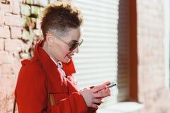 La muchacha está con el móvil en la calle Fotos de archivo