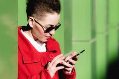 La muchacha está con el móvil en la calle Imagenes de archivo