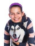 La muchacha está con su perro esquimal del perro Foto de archivo