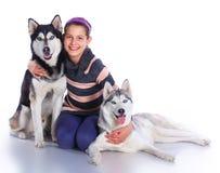 La muchacha está con sus perros fornidos Foto de archivo