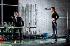 La muchacha está consiguiendo lista para el ejercicio con el instructor Foto de archivo libre de regalías
