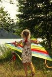 La muchacha está corriendo con la cometa en el día soleado Foto de archivo libre de regalías