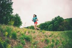 La muchacha está corriendo en terreno áspero fotografía de archivo