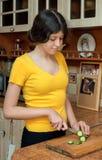 La muchacha está cortando el pepino para la ensalada en la cocina, cocinando el dinne Fotografía de archivo