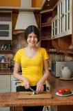 La muchacha está cortando las verduras para la ensalada en la cocina, cocinando dinar Imagen de archivo libre de regalías