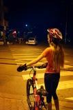 La muchacha está cruzando el paso de peatones de la cebra en la bicicleta en la ciudad de la noche Imagenes de archivo