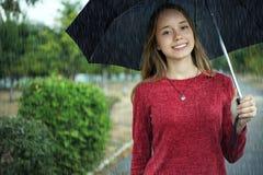 La muchacha está debajo de un paraguas negro Fotos de archivo libres de regalías