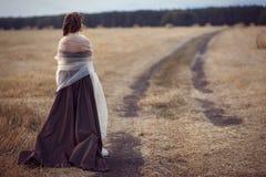 La muchacha está defendiendo en el campo el camino Fotos de archivo libres de regalías