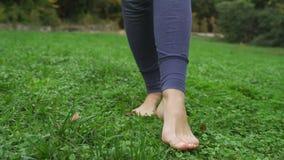 La muchacha está descalzo en la hierba verde almacen de metraje de vídeo