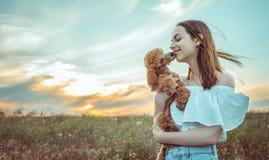 La muchacha está descansando con un perro en un campo Fotografía de archivo libre de regalías