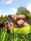 La muchacha está descansando sobre el césped imagenes de archivo