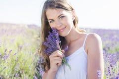 La muchacha está descansando sobre el campo púrpura de la lavanda Imagen de archivo libre de regalías