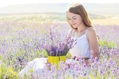 La muchacha está descansando sobre el campo púrpura de la lavanda Imagenes de archivo