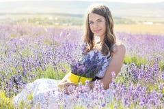 La muchacha está descansando sobre el campo púrpura de la lavanda Fotos de archivo libres de regalías