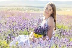 La muchacha está descansando sobre el campo púrpura de la lavanda Foto de archivo