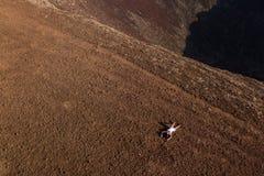 La muchacha está descansando sobre el top de un volcán imágenes de archivo libres de regalías