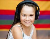 La muchacha está disfrutando de música usando los auriculares Foto de archivo libre de regalías
