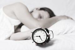La muchacha está durmiendo en cama y está cambiando el despertador la mujer soñolienta sostiene el despertador en su mano y duerm Imágenes de archivo libres de regalías