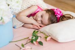 La muchacha está durmiendo en la cama, la flor rosada en su cabeza y el flo Imagen de archivo